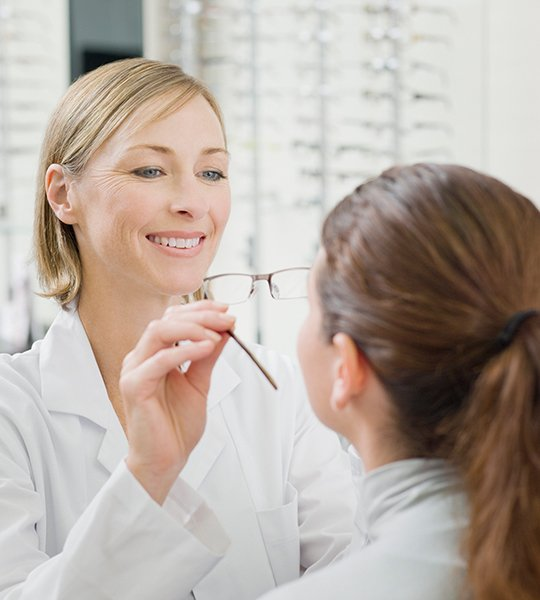 Staff member placing glasses on customer's face